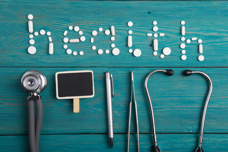 Health concept - pills, stethoscope, clipboard  on the wooden desk