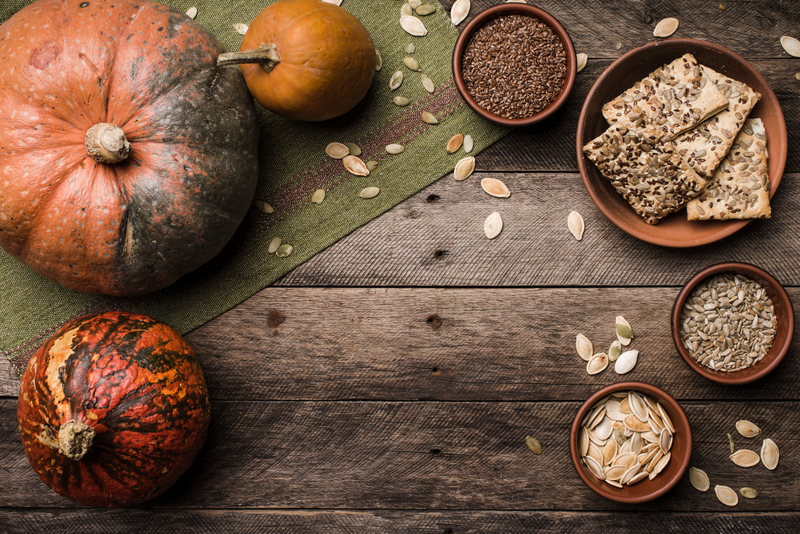 Rustic style pumpkins with cookies and seeds on wood. Autumn Season food photo